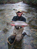 Picture of Altamont Anglers Guide Forrest Marshall holding a large rainbow trout caught on the Davidson River