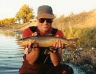 Picture of Drake Whitlock holding a large brown trout