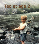 picture of 2 year-old Teo Whitlock with fly rod in hand on banks of a trout stream